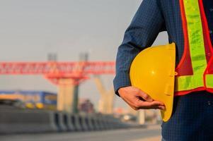 Techniker, der gelben Hut Schutzhelm Sonnenlicht Hintergrund hält foto
