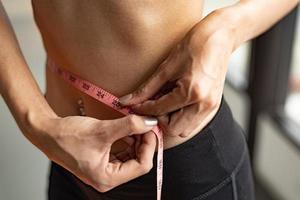 Nahaufnahme des Sports glückliche schlanke Frau mit Taillenbandlinie foto