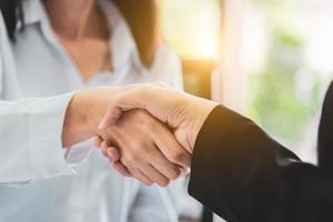 Nahaufnahme von Geschäftsleuten, die nach Abschluss der Vereinbarung die Hände schütteln foto