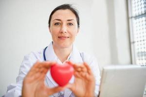 Der Arzt des medizinischen Kardiologen hält ein rotes Herz, das dem Patienten gegeben wird foto