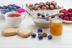 ein gesundes Frühstück mit Haferflocken, Blaubeeren, Himbeeren, Haselnüssen foto