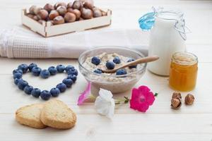 Liebesfrühstück aus Haferflocken Blaubeeren mit Herzen, Honig foto