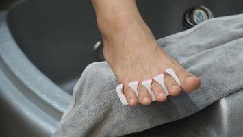 Fußpflege. Frau nackte Füße massieren in Seifenwassermaschine im Spa-Shop. foto