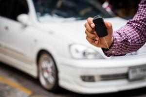 Hand hält Autoschlüssel mit Auto im Hintergrund foto
