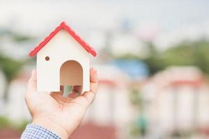 Hand, die Modellhaus hält. Immobilienkreditversicherung foto