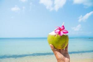 Nahaufnahme Hände Mann mit Kokosnuss am tropischen Strand. foto