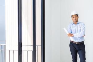 junger asiatischer ingenieur oder architekten, der den grundrissplan des gebäudes hält. foto