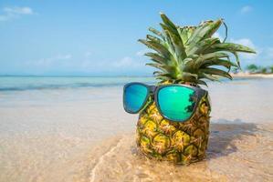 Ananas mit Sonnenbrille auf tropischem Strandhintergrund. Sommerkonzept foto