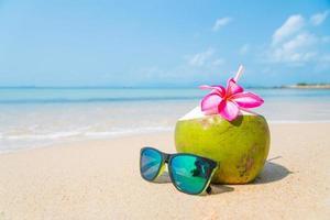Kokosnuss und Sonnenbrille am tropischen Strand. foto