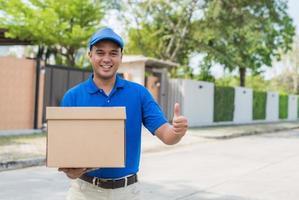 Mann in blauer Uniform und Paketkarton ausliefern foto