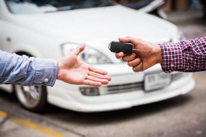 Hand, die Autoschlüssel auf Autohintergrund gibt foto