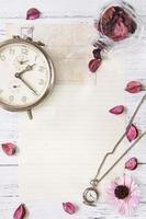 Blumenblätter Briefumschlag Glasflasche Taschenuhr foto