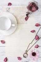 Blumenblätter Briefumschlag Glasflasche Taschenuhr Teetasse foto