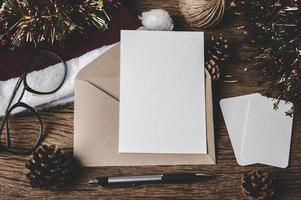 Umschlag, Blankokarte, Brille und ein Stift werden auf Holz gelegt. foto