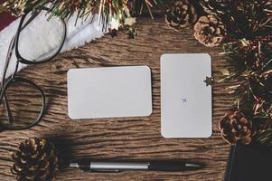 Eine leere Karte, eine Brille und ein Stift werden auf Holz gelegt. foto