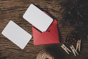 zwei leere Karte mit rotem Umschlag und Wäscheklammer wird auf Holz gelegt. foto