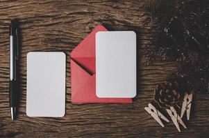 zwei leere karte mit rotem umschlag und stift ist auf holz gelegt. foto