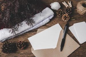 Umschlag, leere Karte und ein Stift werden auf Holz gelegt. foto