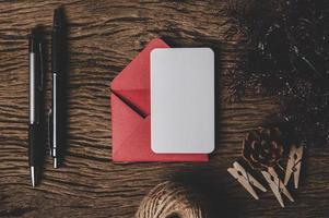 Eine leere Karte mit rotem Umschlag und zwei Stiften wird auf Holz gelegt. foto