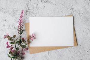 eine leere Karte mit Umschlag und Blume wird auf weißem Hintergrund platziert foto