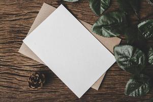 eine leere Karte wird auf Umschlag und Blatt mit Holzhintergrund gelegt foto