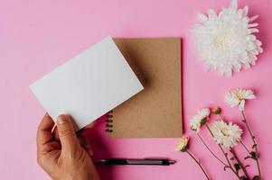 Hand, die leere Karte, Notizbuch, Stift und Blume auf rosa Hintergrund hält foto