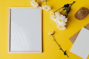 Whiteboard mit Umschlag und Blume ist auf gelbem Hintergrund platziert foto