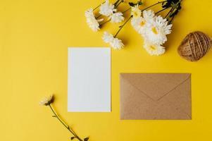 eine leere Karte mit Umschlag und Blume wird auf gelben Hintergrund gelegt foto