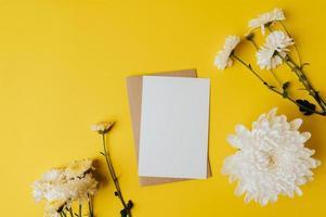 eine leere Karte mit Umschlag und Blumen wird auf gelben Hintergrund gelegt foto