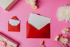 roter Umschlag, rosa Geschenkbox mit Blankokarte und Blume auf rosa foto
