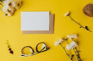 Blankokarte mit Umschlag, Brille und Blume wird auf Gelb gelegt foto