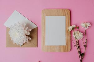 brauner Umschlag, Blume und Blankokarte auf Holzplatte mit rosa foto