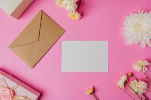 brauner Umschlag, rosa Geschenkbox mit Blankokarte und Blume foto