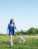 Junge attraktive Frau, die am Sommertag mit ihrem Hund im Park spazieren geht foto