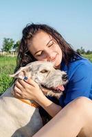 junge fröhliche Frau, die mit ihrem Hund im Park spielt foto