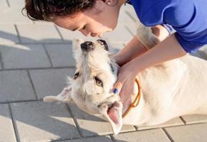 junge attraktive Frau, die ihren Hund auf der Straße küsst foto