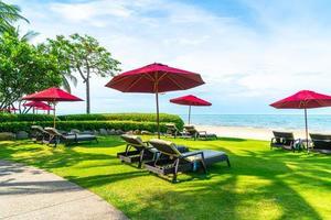 Strandkorb und Sonnenschirm mit Meeresstrand Hintergrund foto