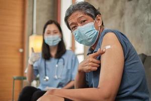 älterer Patient zeigt nach der Impfung mit dem Finger auf den Arm. foto