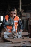 Der junge kaukasische Tischler arbeitet in einer Holzsägewerksfabrik. foto