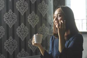 entspannt lächelnde asiatische frau, die kaffee trinkt, während sie wegen der arbeit anruft foto