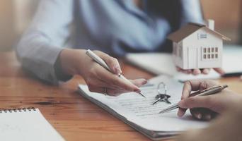 Bild eines Immobilienmaklers, der dem Kunden bei der Unterzeichnung des Vertragsdokuments hilft foto