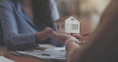 Immobilienmakler, der dem Kunden nach Vertragsunterzeichnung Hausschlüssel übergibt foto