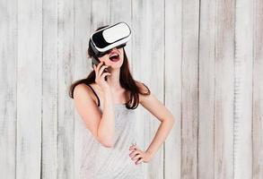 hübsches Mädchen mit VR-Brille, das mit dem Handy spricht foto