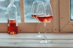Flasche Roséwein und zwei Gläser auf einem Fensterbrett foto