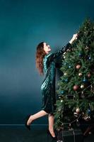 charmante lächelnde junge Frau, die den Weihnachtsbaum schmückt foto
