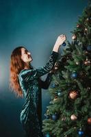 attraktive lächelnde frau, die weihnachtsbaum schmückt foto