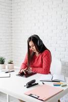 junge Frau in schwarzen Kopfhörern, die online Englisch mit Tablet unterrichtet foto