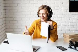 Frau studiert online mit Laptop und zeigt Daumen nach oben foto