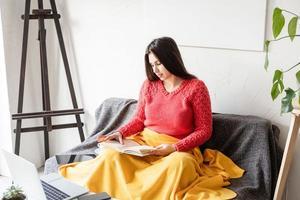 Frau liest in lässiger Kleidung auf dem Sofa sitzend foto