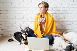 Frau sitzt mit ihren Hunden auf dem Boden und trinkt Kaffee foto